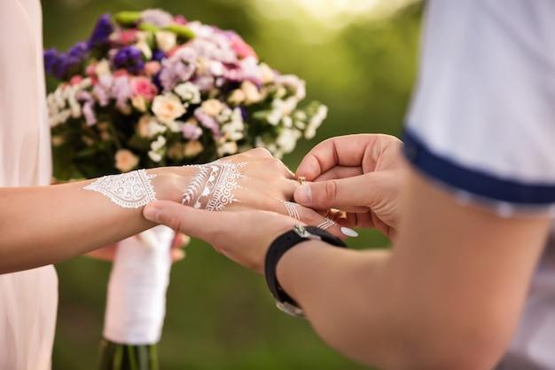 Voorstel van huwelijk of verloving van indisch paar. verlovingsring aan kant van meisje met mehendi ornament bij huwelijksceremonie Premium Foto