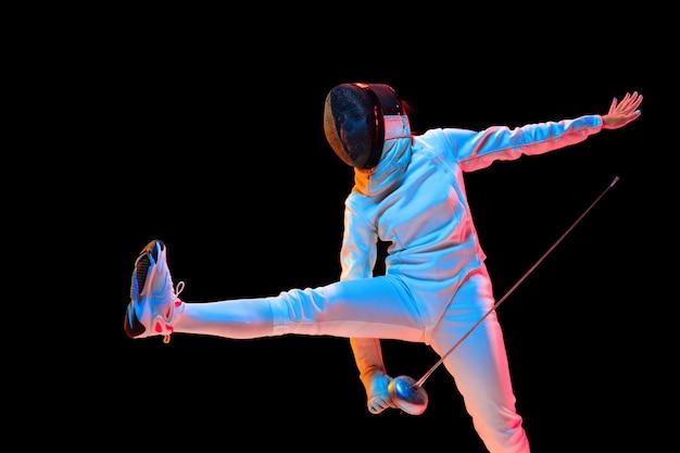 Vooruit. tienermeisje in hekwerkkostuum met in hand zwaard geïsoleerd op zwarte muur, neonlicht. jong model oefenen en trainen in beweging, actie. copyspace. sport, jeugd, gezonde levensstijl. Gratis Foto