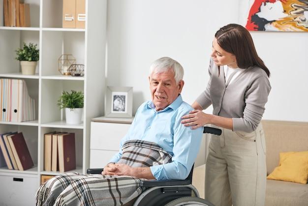 Voorzichtige jonge verpleegster in gesprek met oudere man in rolstoel tijdens een bezoek aan hem thuis Premium Foto