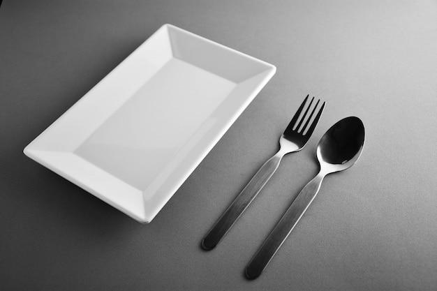 Vork, lepel en een vierkante witte keramische schaal Premium Foto