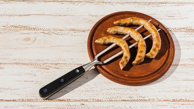 Vork met gebraden worsten op schotel Gratis Foto