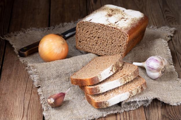 Vorm rogge-tarwebrood, gesneden stukken, uien en knoflook op een natuurlijk servet. Premium Foto