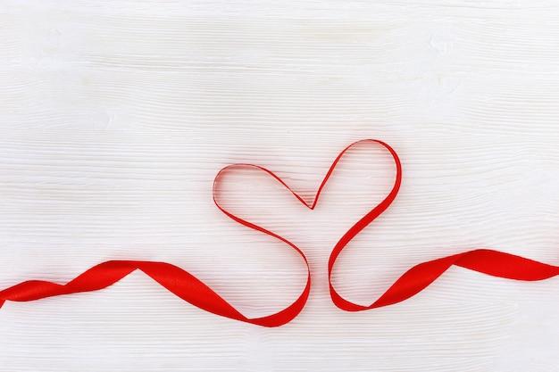 Vorm van hart van rood lint op wit hout Premium Foto