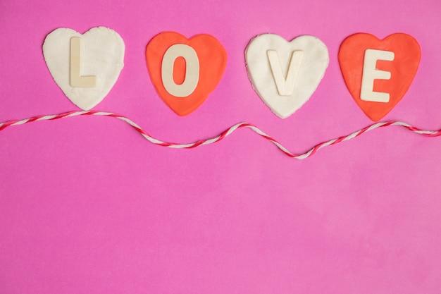 Vorm van hart, woord liefde in rode harten op roze achtergrond, liefde pictogram, valentijnsdag Premium Foto