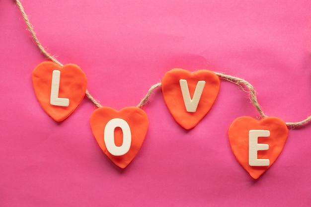 Vorm van hart, woord liefde in rode harten op roze achtergrond Premium Foto