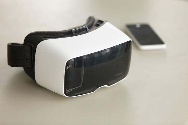 Vr-hoofdtelefoon en smartphone op bureau, virtuele werkelijkheids mobiele technologie Gratis Foto