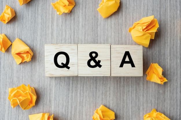 Vraag- en antwoordwoord met houten kubusblok en geel verkruimeld papier Premium Foto