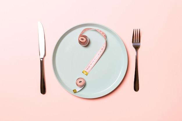 Vraagteken gemaakt van meetlint op ronde plaat op roze Premium Foto