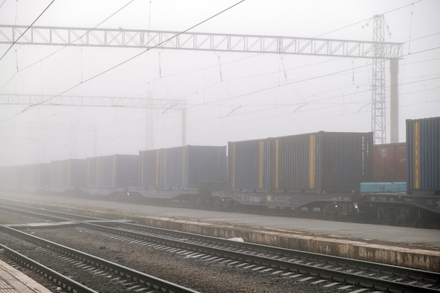 Vracht trein verplaatsen op platform goederentrein station passeren. wagens rijdt op stalen spoorweg. zware industrie transport concept. Premium Foto