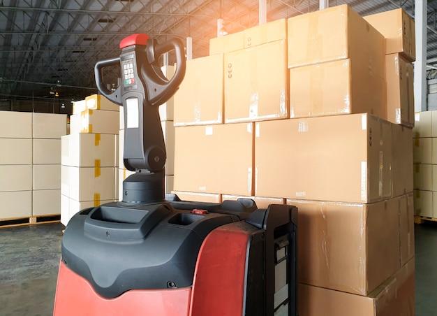 Vrachtdozen verzending verpakking fabriek en opslag stapel kartonnen dozen op pallet en vorkheftruck palletkrik bij de opslag van het magazijn Premium Foto