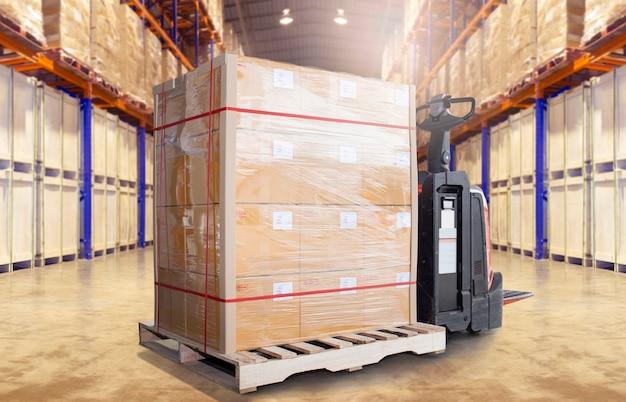 Vrachtpalletverzending en elektrische heftruckpalletkrik in de magazijnopslag. Premium Foto