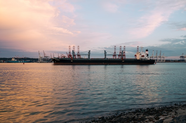 Vrachtschip dat bij de haven op een zonnige dag tijdens zonsondergang wordt geparkeerd Gratis Foto