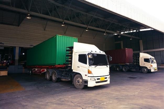Vrachtwagen industrieel met groene en rode containerwerf met vorkheftruck die in groot ladingspakhuis werken voor logistiek. Premium Foto