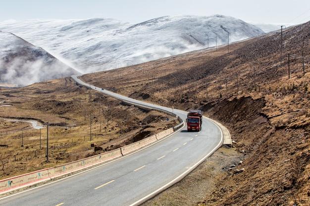 Vrachtwagen op de weg, mooie de winterweg in tibet onder sneeuwberg sichuan, china. Premium Foto