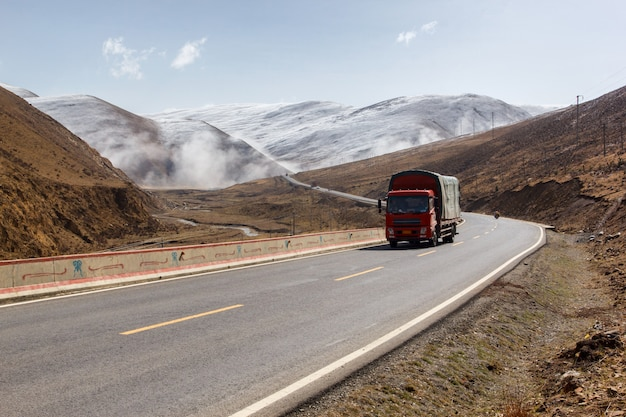 Vrachtwagen op de weg, mooie de winterweg in tibet onder sneeuwberg sichuan china Premium Foto