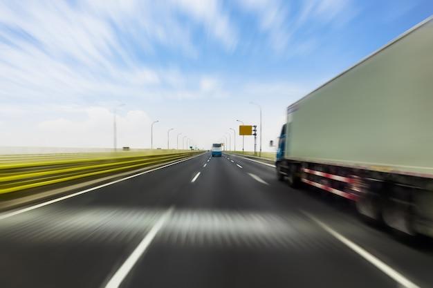 Vrachtwagen op een snelle uitdrukkelijke weg, bewegingsonduidelijk beeld Premium Foto