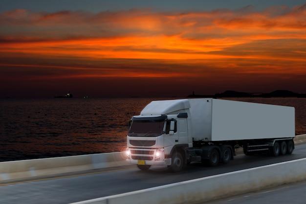 Vrachtwagen op wegweg met container, logistisch industrieel vervoer met zonsopganghemel Premium Foto