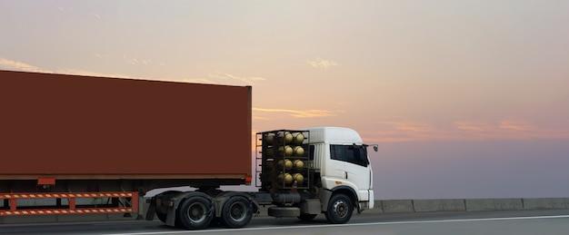 Vrachtwagen op wegweg met rode container, logistische industrieel met zonsopganghemel Premium Foto
