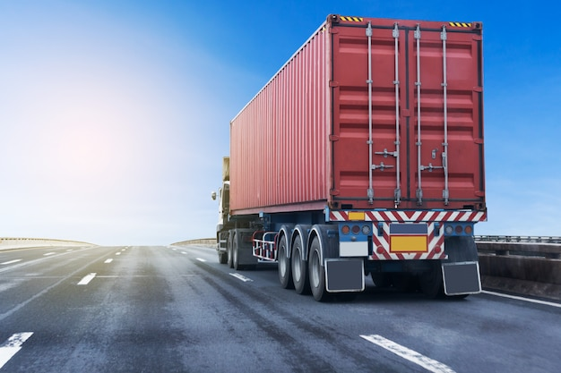 Vrachtwagen op wegweg met rode container. vervoer op de asfalt snelweg Premium Foto