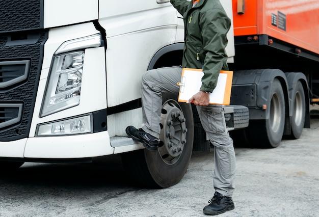Vrachtwagenchauffeur houden een klembord met semi-vrachtwagen. Premium Foto