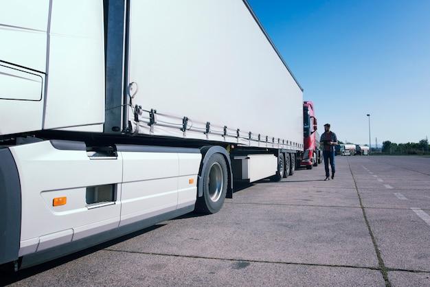 Vrachtwagenchauffeur inspecteert vrachtwagen lang voertuig voordat hij gaat rijden Gratis Foto
