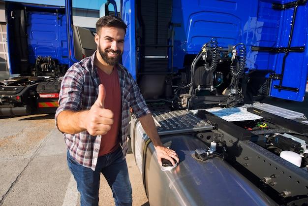 Vrachtwagenchauffeur opent reservoirtank om de vrachtwagen bij te tanken en houdt zijn duimen omhoog Gratis Foto