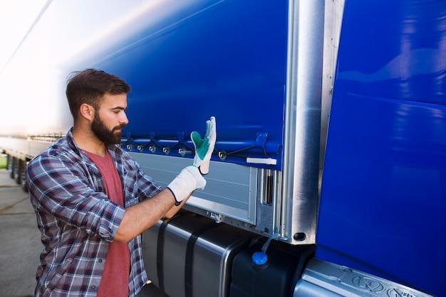 Vrachtwagenchauffeur trekt handschoenen aan om het dekzeil van het voertuig te verwijderen voor het lossen Gratis Foto