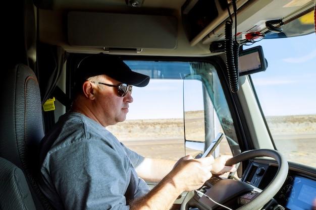 Vrachtwagenchauffeurs grote vrachtwagenchauffeur in cabine van grote moderne vrachtwagen Premium Foto