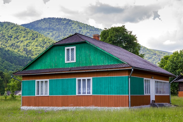 Vreedzame landelijke zomer landschap op zonnige dag. verlicht door de zon prachtige houten woonhuis geschilderd in groene, blauwe en bruine kleuren op met gras begroeide bloeiende weide op beboste bergen. Premium Foto