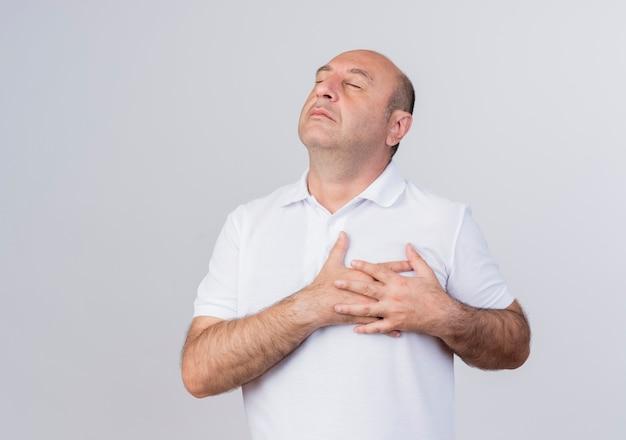 Vreedzame toevallige volwassen zakenman die handen op hart zetten dat op witte achtergrond met exemplaarruimte wordt geïsoleerd Gratis Foto