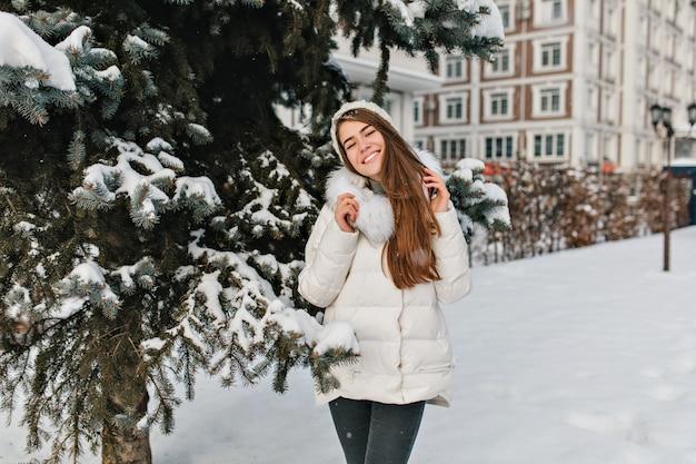 Vreugde, geluk van geweldig mooi meisje glimlachend in warme winterkleren op vr boom vol met sneeuwruimte. Gratis Foto