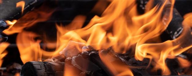 Vreugdevuur in de barbecue, brandhout brandt, vlam van vuur, horizontaal Premium Foto