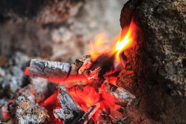 Vreugdevuur met oranje vlammen en brandhout Premium Foto