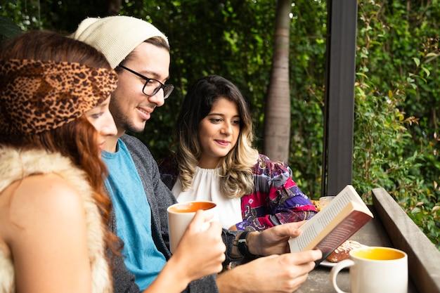 Vriend die een boek leest bij koffiewinkel Gratis Foto