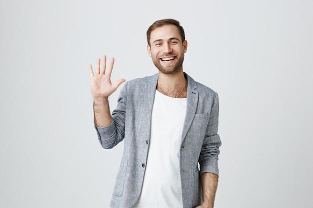Vriendelijk lachende knappe jongen zwaaien hand in groet, zeg hallo Gratis Foto
