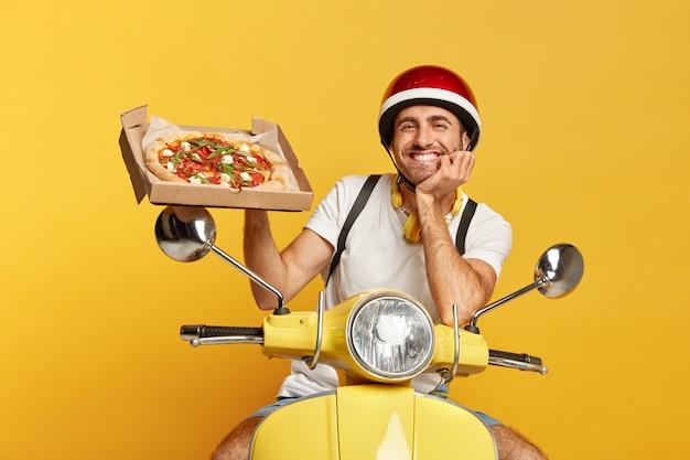 Vriendelijk ogende bezorger met helm gele scooter rijden terwijl pizzadoos vasthoudt Gratis Foto