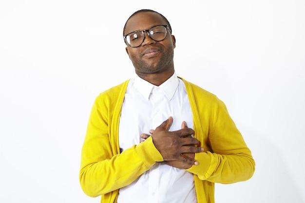 Vriendelijk ogende dankbare afro-amerikaanse man die de handen op zijn borst houdt, medeleven, erkenning en dankbaarheid toont, opgewekt of gevleid is. positieve menselijke emoties en lichaamstaal Gratis Foto