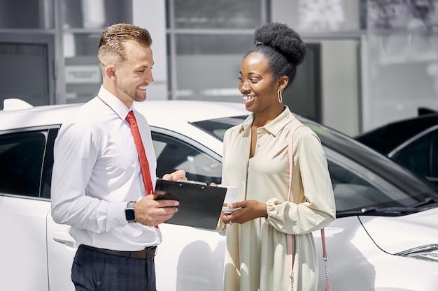 Vriendelijke blanke verkoper praat met zwarte klant vrouw Premium Foto