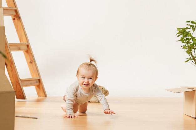 Vriendelijke blauwe ogen babymeisje, zittend op de vloer binnenshuis Gratis Foto