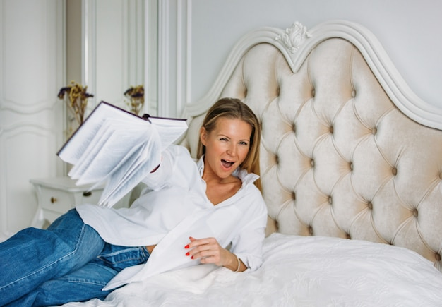 Vriendelijke charmante blondevrouw met lang eerlijk haar in vrijetijdskleding met boek op het bed in helder rijk binnenland Premium Foto