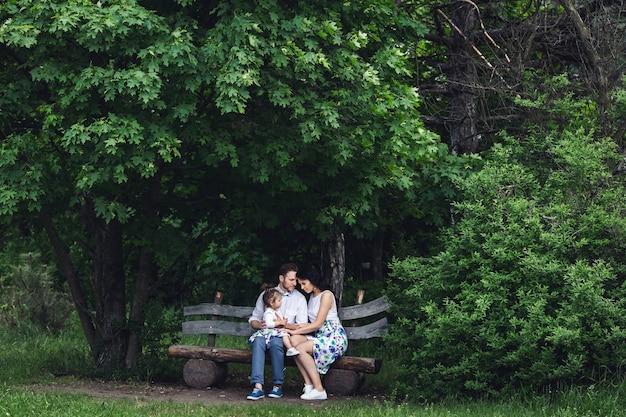 Vriendelijke en gelukkige familie rusten op een houten bankje onder de esdoorn. Premium Foto