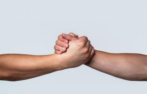 Vriendelijke handdruk, groeten van vrienden, teamwerk, vriendschap. redding, helpend gebaar of handen. Premium Foto