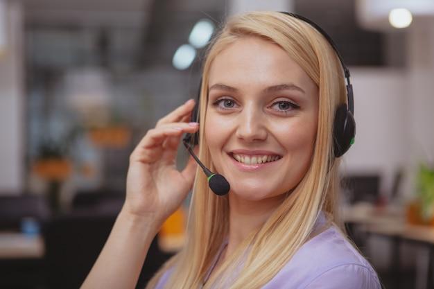 Vriendelijke klantondersteuningsexploitant met hoofdtelefoon die bij call centre werkt Premium Foto