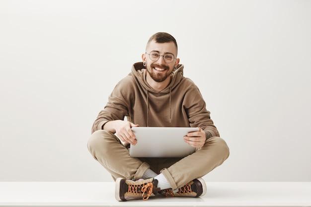 Vriendelijke knappe jongeman zitten met laptop en glimlachen Gratis Foto