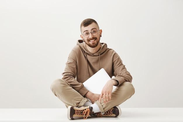 Vriendelijke knappe man zitten op de vloer met laptop en glimlachen Gratis Foto