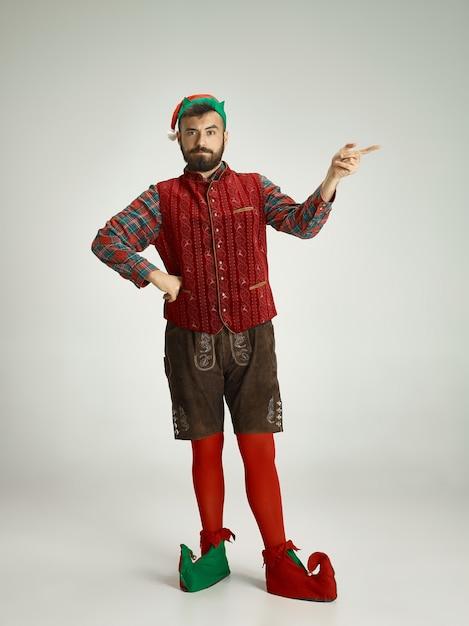 Vriendelijke man gekleed als een grappige kabouter die zich voordeed op een afgelegen grijs Gratis Foto