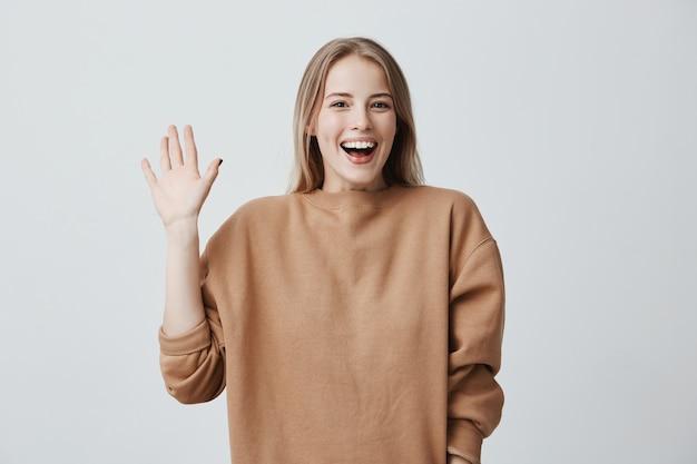 Vriendelijke positieve blonde vrouw glimlachend breed en gelukkig, groet met de hand, blij om ze te ontmoeten. positieve emoties, gevoelens en gezichtsuitdrukking. Gratis Foto