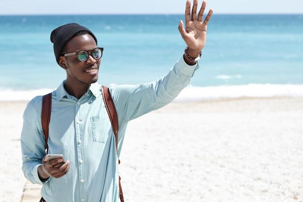 Vriendelijke positieve glimlachende jonge afro-amerikaanse man in trendy hoed en tinten met smartphone en wuivende hand, begroet vrienden terwijl het lopen op stadsstrand Gratis Foto
