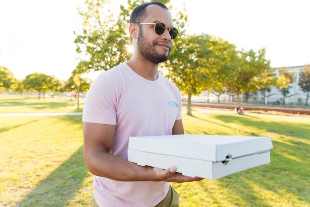 Vriendelijke positieve knappe kerel die pizza draagt Gratis Foto