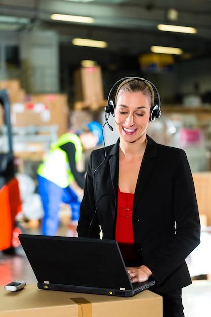 Vriendelijke vrouw, dispatcher of supervisor met behulp van headset en laptop in magazijn van expeditiebedrijf, een vorkheftruck Premium Foto